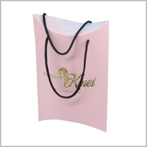 Pink pillow boxes with handle for hair bundles packaging. The handle formed by black thin hemp rope can facilitate customers to carry packaging and products.