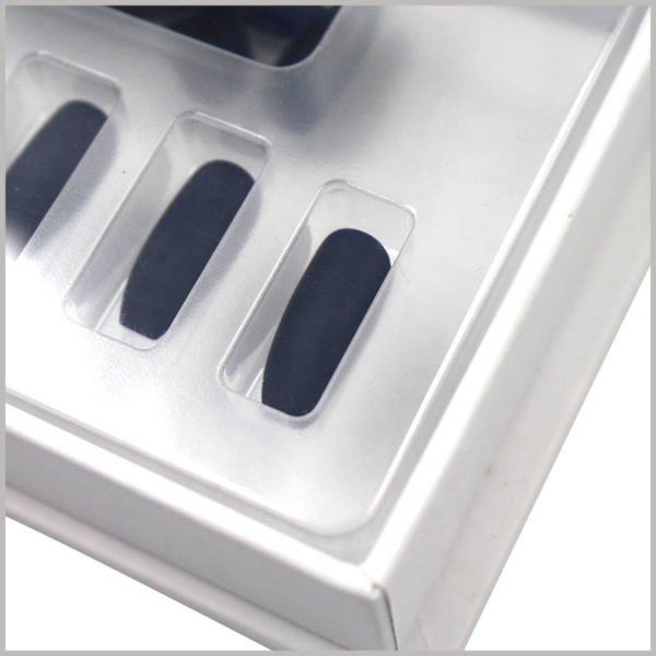 White cardboard nail boxes with clear blister. The blister pack is placed inside the box to fix the black false nails in a specific position, arranged and displayed in a specific way.