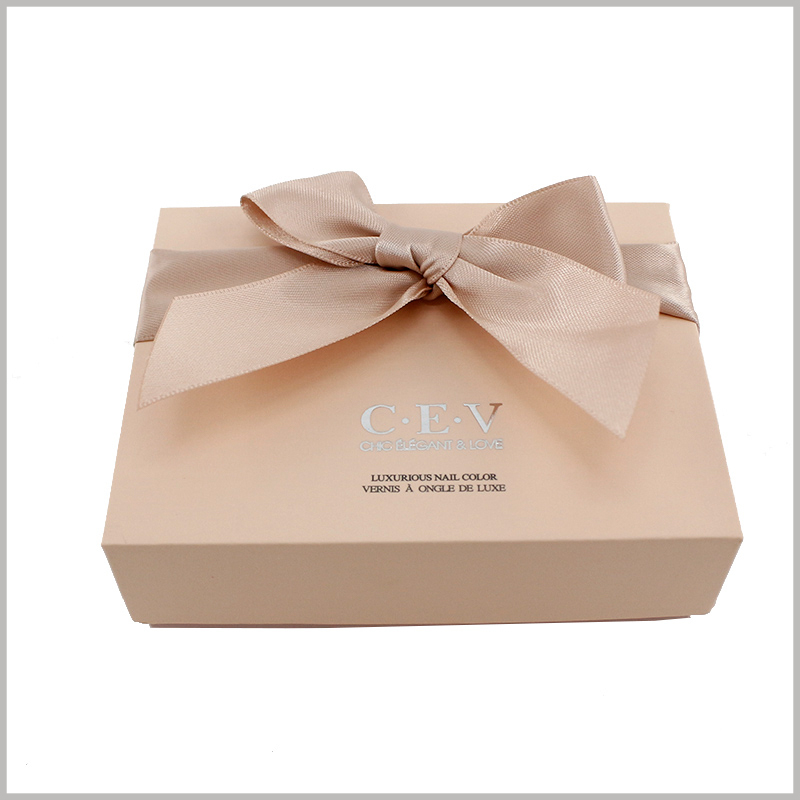 custom nail polish gift boxes packaging. Square cardboard cardboard cosmetic boxes are covered with gift bows on the top, and the relevant information of the brand is printed to improve customers' awareness of the products.